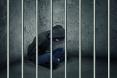Burglar in jail. Catch the burglar concept, thief with balaclava caught and sitting in the jail royalty free stock photo