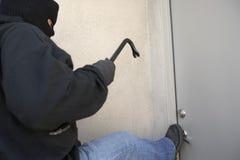 Burglar Kicking Door Of House. Burglar with crowbar kicking the door of house royalty free stock images