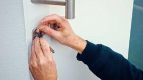 Burglar with lock-picking break door to enter the house stock video