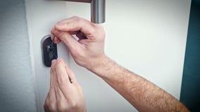 Burglar with lock-picking break door to enter the house stock footage