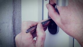 Burglar with lock-picking break door to enter the house stock video footage