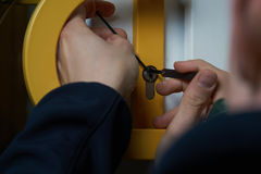 Burglar with lockpick tool opens the front door to enter the house. Also key service or locksmith. Intruder or Burglar with lockpick tool opens the front door to royalty free stock photo