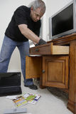 Burglar Looking Through Drawers In House. Caucasian male burglar looking through drawers in house royalty free stock photography