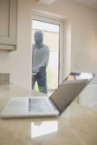 Burglar looking at laptop through the window Stock Photo