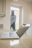 Burglar looking at laptop through the window. Of kitchen stock photo