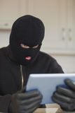 Burglar looking at tablet pc Royalty Free Stock Images