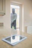 Burglar looking at tablet pc through kitchen door Royalty Free Stock Image