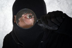 Burglar with magnifying glass Stock Images