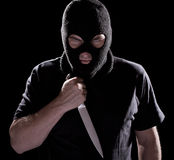 Burglar in mask holding knife. On black background Royalty Free Stock Photos