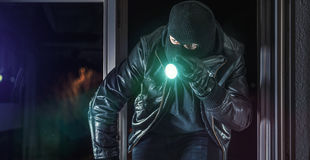 Burglar. Masked burglar with crowbar breaking and entering into a house - shot with dramatic motion Royalty Free Stock Photos