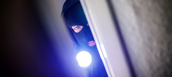 Burglar. Masked burglar with crowbar breaking and entering into a victim`s home Stock Photo