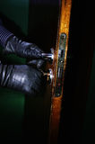 Burglar in the night. Closeup of burglar hands in leather gloves opening a door in the night with selective focus stock images