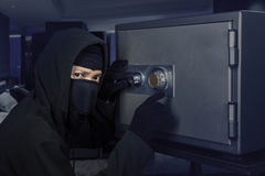 Burglar opening bank vault. Male burglar wearing a mask and trying to steal a bank vault in the bedroom at home royalty free stock photo