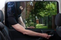 Burglar opening car door Royalty Free Stock Photos