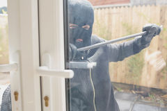 Burglar opening the door with a crowbar Stock Photos