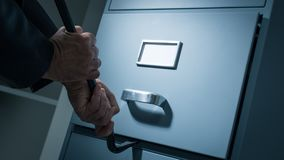 Data theft and security. Burglar opening a drawer in the office at night using a crowbar, he is stealing confidential data and information, data theft and stock photography