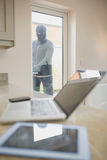 Burglar opening kitchen door and looking at laptop. On counter of kitchen royalty free stock photos