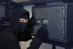 Burglar opening safe-deposit box. Picture of a male burglar wearing a mask and trying to steal a safe deposit box in the office Stock Images