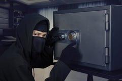 Burglar opening safe-deposit box Stock Images
