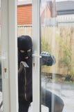 Burglar opening the terrace door Royalty Free Stock Photography