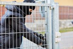 Burglar opens door lock of a gate. Burglar opens door lock from a locked gate royalty free stock photo