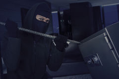 Burglar opens safe deposit with crowbar. Male burglar wearing a mask and using a crowbar to open a safe deposit in the bedroom Stock Photos