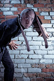 Burglar with pantyhose on face. Burglar sneaking by brick wall with pantyhose disguise over head and face royalty free stock images