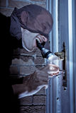 Burglar picking door lock. A burglar holding a flashlight in his mouth, picking the lock of a door royalty free stock photography