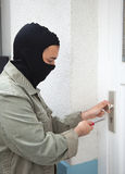 Burglar at a private home. Burglar with mask at the door of a private home stock photos