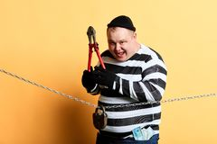 Burglar with scissors in hands looking at the camera while standing behind the chain. Happy burglar with scissors in hands looking at the camera while standing royalty free stock photos