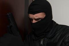 Burglar Standing Behind The Door With A Gun