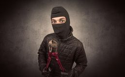 Burglar with tool. Burglar standing in black clothes and balaclava on his head stock photo