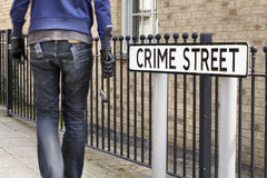 Burglar standing on street with crowbar Royalty Free Stock Images