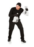 Burglar: Stealing Money Bags. Series with Caucasian male as a burglar or thief, sneaking in a window, carrying stolen goods, etc.  Isolated on white background Royalty Free Stock Images