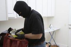 Burglar Stealing Money From House. Burglar in balaclava stealing money from wallet stock photos