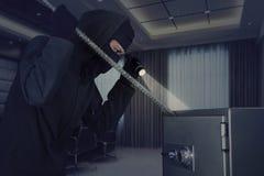 Burglar stealing a safe deposit box Stock Photography