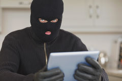 Burglar stealing the tablet pc. In kitchen stock photo