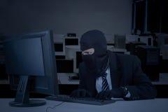 Burglar takes data on computer Royalty Free Stock Photo