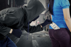 Burglar taking money from pocket of victim Royalty Free Stock Images