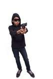 Burglar or terrorist in black mask shooting with gun isolated on Stock Photos