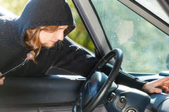 Burglar thief breaking into car and stealing. Anti theft system problem concept. Burglar thief man wearing black clothes breaking into car and stealing something royalty free stock photos