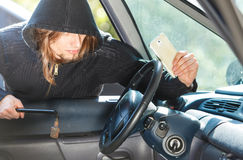 Burglar thief breaking into car stealing smartphone Stock Image