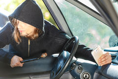Burglar thief breaking into car stealing smartphone. Anti theft system problem concept. Burglar thief man wearing black clothes breaking into car and stealing stock photography