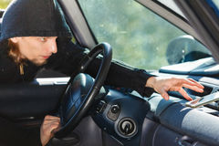 Burglar thief breaking into car stealing smartphone. Anti theft system problem concept. Burglar thief man wearing black clothes breaking into car and stealing royalty free stock photo