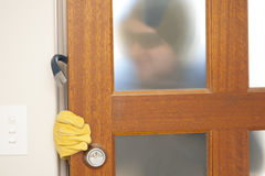 Burglar breaking in house with crowbar Stock Photos
