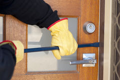 Burglar breaking in house with crowbar at door Royalty Free Stock Photo