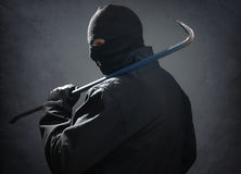 Burglar. Or thief holding a crowbar in the dark Stock Photo