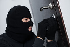 Burglar thief at house breaking. Thief Burglar force lock metal door with a tool during house breaking Stock Photography
