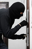 Burglar thief at house breaking. Thief Burglar opening metal door with a crowbar during house breaking Royalty Free Stock Photo