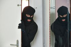 Burglar thief at house breaking. Thief burglar opening door during house breaking penetration Stock Photo